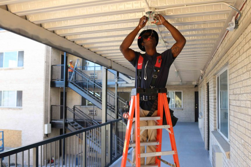 A construction worker installs high efficiency lighting at an multifamily affordable housing property